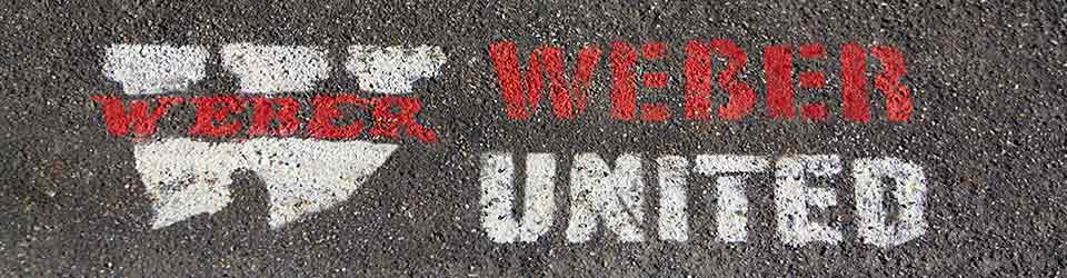 "stencil on asphalt with Weber logo and ""Weber United"""